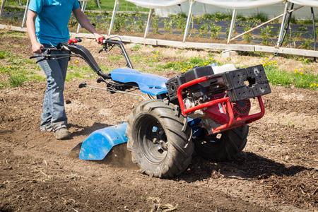 Woman worker driving rototiller tractor unit preparing soil on outdoor garden