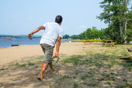 adult man throwing horseshoe game beach activity QC Canada