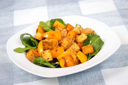 tofu sweet and sour with bell peppers over spinach bed