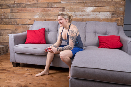 blond woman playing video games and having fun in the living room of a modern house Archivio Fotografico