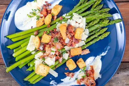 caesar asparagus with sliced parmesan cheese bacon and crouton gourmet cuisine dish closeup