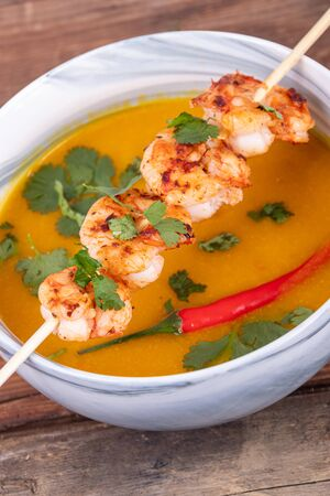 Delicious grilled spicy shrimps skewer over smooth squash curry soup bowl wood background