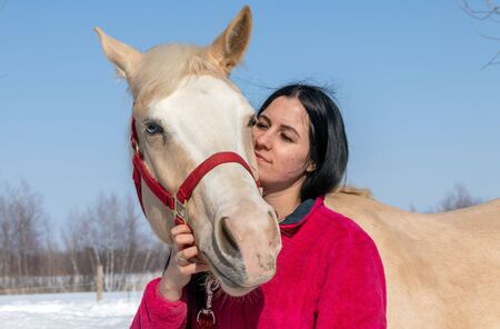 portrait of a woman and her palomino male horse outside in winter
