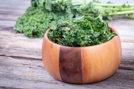 healthy homemade seasoned green kale chips snack on a wooden bowl over a plank table