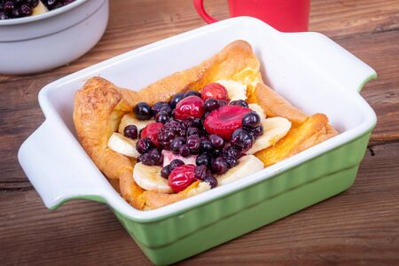 dutch German pancake topped with bluberries berries fruit and banana breakfast over table
