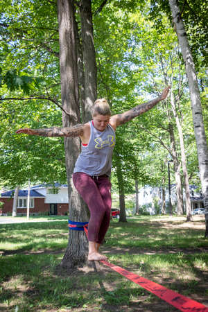 Sorel-Tracy, Canada-28 July 2020 : Smiling woman taking a break on a Base Line Slack Line recreational balance sport  in the park at summer Editorial