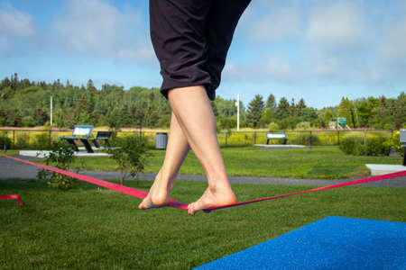 closeup feet walking over a slackline tightrope at the park Imagens
