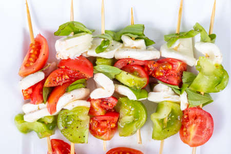tomato basil and mozzarella cheese antipasti on a stick plate closeup Imagens