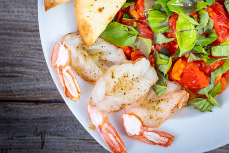 garlic butterfly prawn with roasted tomatoes dish Imagens