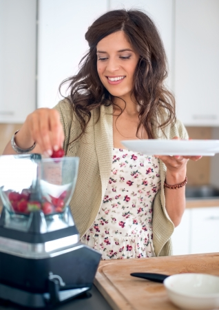 Portrait of a girl using the blender to prepare raw banana ice cream with strawberries photo