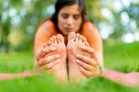 Feet detail of a girl meditation and taking a yoga pose at sunset under trees