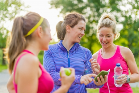 Group of happy active girls preparing for a run in nature by choosing music on smart phone Standard-Bild