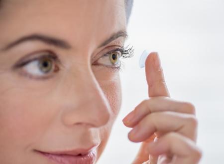 lentes de contacto: de cerca de una atractiva mujer madura en ponerse los lentes de contacto en sus ojos verdes Foto de archivo