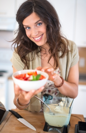 Attractive woman preparing fruits in the blender photo