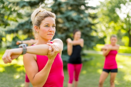 Portrait of a concentrated young woman streching her arm before jogging with friends