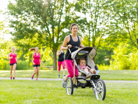 Woman pushing her little girl in a toddler while running outside with friends Standard-Bild