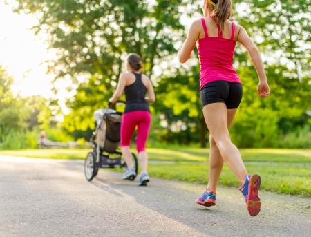 people jogging: Mujer que empuja a su ni�a en un ni�o mientras se ejecuta al aire libre con los amigos al atardecer