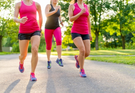 only young women: group of healthy girls running outdoors at sunset with lens flare  Stock Photo