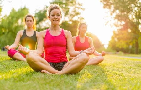horizontal detail of women doing yoga outdoors at sunset with lens flare  Defocused