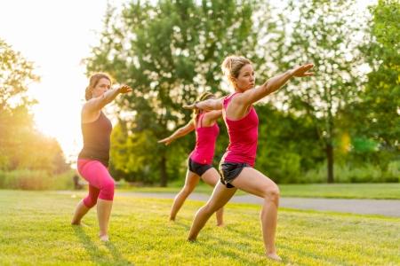 fitness training: horizontale groep van vrouwen die de krijger yoga pose buitenshuis bij zonsondergang met lens flare Stockfoto