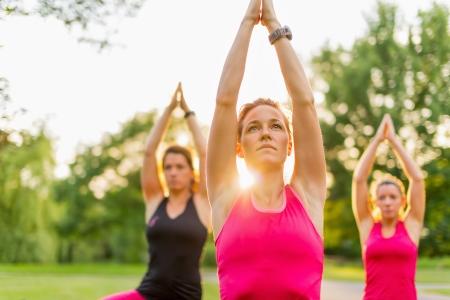 lens flare: Dettaglio orizzontale delle donne facendo yoga all'aperto al tramonto con lens flare Sfocato