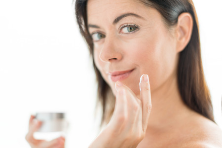 Mature lady using lotion to prevent wrinkles Banco de Imagens