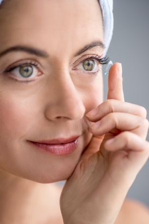 Attractive mature lady putting on contact lenses in her eyes Stock Photo