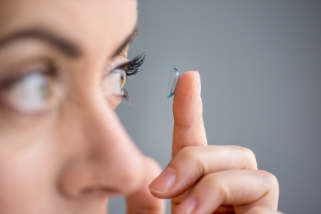 contact: Attractive mature lady putting on contact lenses in her eyes Stock Photo