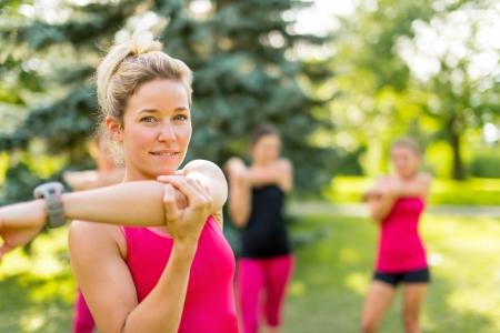 Vrolijke jonge vrouw streching haar arm voordat joggen