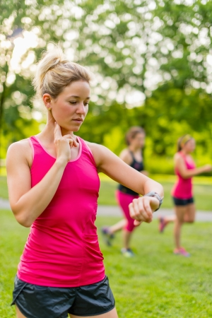 mesure: Portrait of an athlete using her watch to mesure her pulse Stock Photo