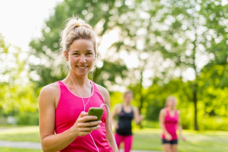 Portrait of a woman using her smart phone for a workout photo