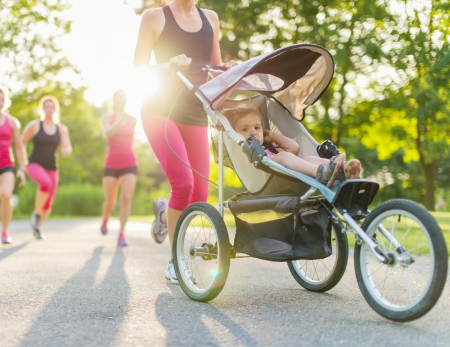 Exercising: Woman pushing her toddler while running in nature with friends