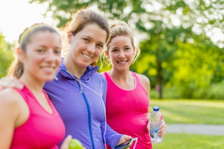 Group of female joggers laughing while using a smart phone photo