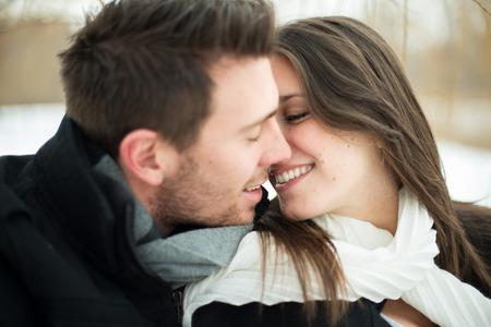 魅力的な異性愛のカップルが雪の毛布の上キス