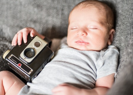 0 3 months: hipster baby holding a vintage camera Stock Photo