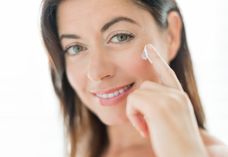 portrait of a mature lady preventing wrinkles with a face lotion
