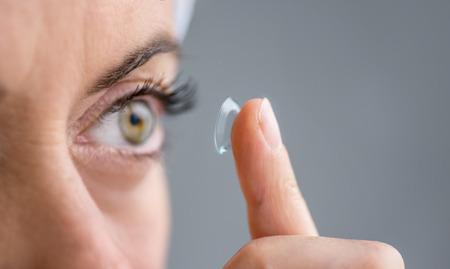 lentes de contacto: primer plano de una mujer madura de ponerse los lentes de contacto en sus ojos