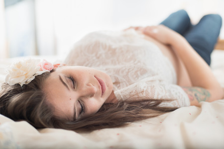 Defocused picture of a romantic and feminine pregnant woman with pink flowers photo