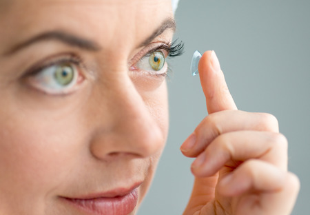 contact: close up of a mature lady putting on contact lenses in her eyes