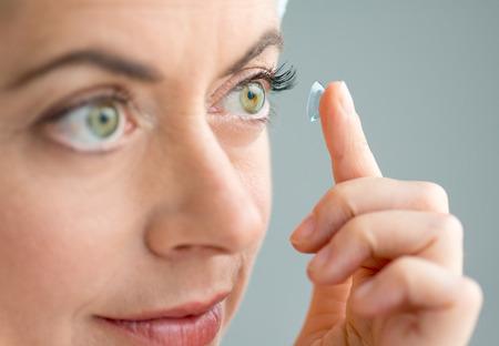 close-up van een rijpe dame aantrekken van contactlenzen in haar ogen