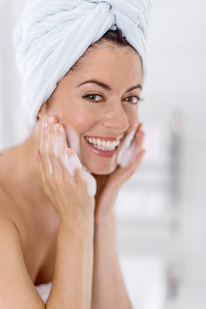 portrait of a beautiful mature lady using soap and water to purify and clean her face photo
