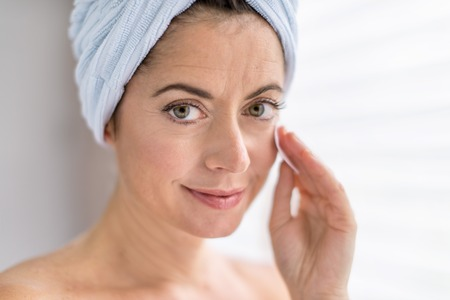portrait of a beautiful mature lady using a cotton pad to clean her skin and remove her make up