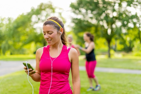 chose: Portrait of an attractive woman using her smart phone to chose songs for a workout Stock Photo