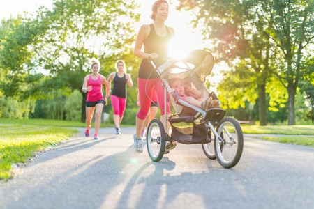jogging in park: Woman pushing her little girl in a toddler while running in nature with friends Stock Photo