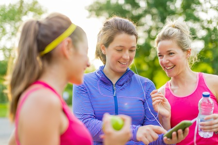 Group of three female joggers laughing while using a smart phone to choose music