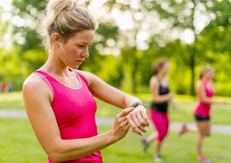 Portrait of an athlete using her watch to mesure her pulse while running with friends photo