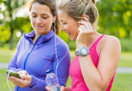 Group of two female joggers laughing while using a smart phone to choose music  photo
