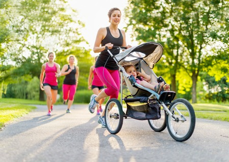 Woman pushing her little girl in a toddler while running in nature with friends Standard-Bild