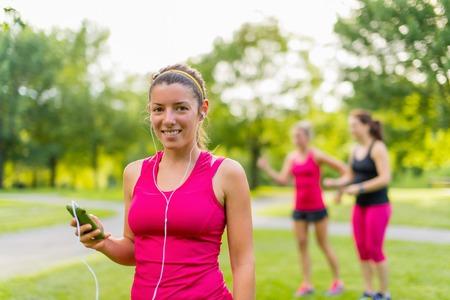 chose: Ritratto di una donna attraente usando il suo telefono intelligente di scegliere le canzoni per un allenamento Archivio Fotografico