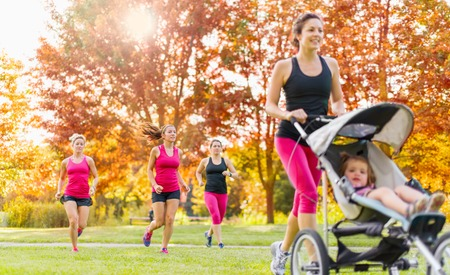 Woman pushing her little girl in a toddler while running in nature with friends photo